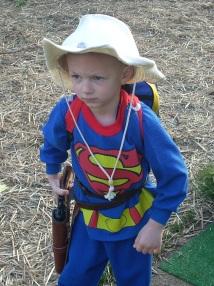 Boy Twin practicing his cowboy walk, wearing superhero pajamas and a Dr. Seuss backpack.